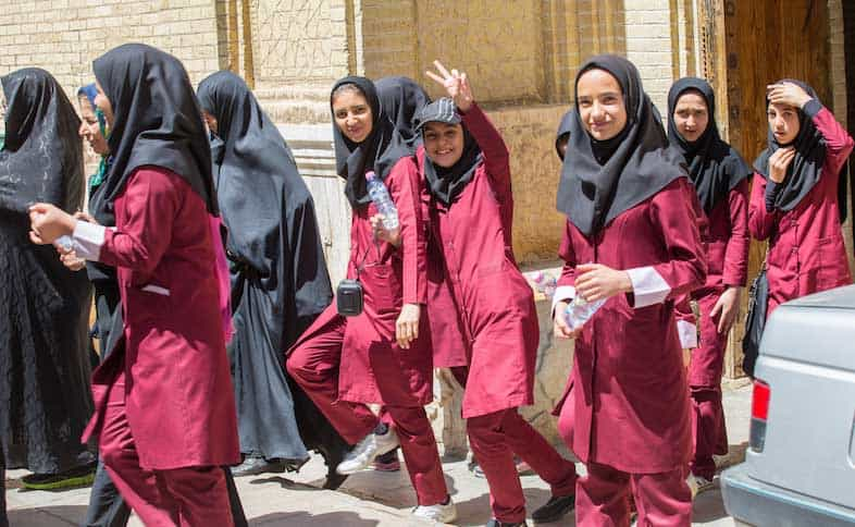 School girls in uniforms and headscarves are released from school