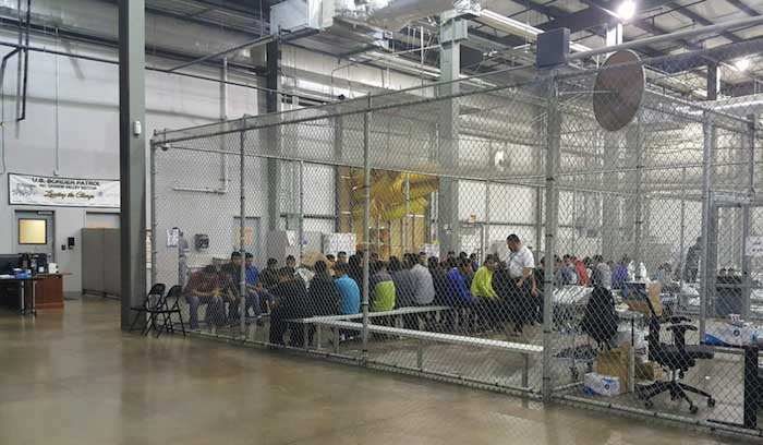 US border detention center with migrants in caged area