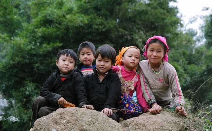 A groupo of Vietnamese children crouching on a rock