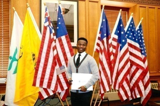 Wilson Kubwayo in front of flags at his citizenship ceremony