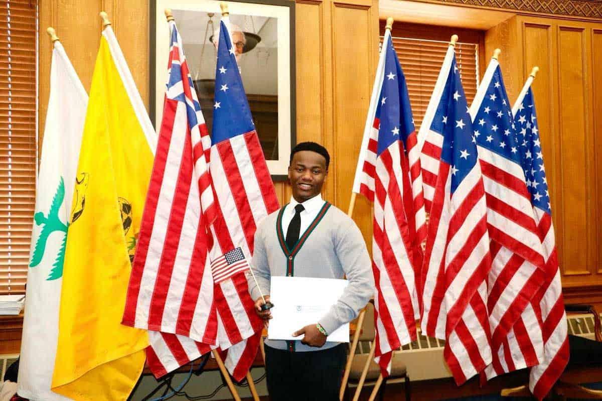 ويلسون كوبوايو أمام الأعلام في مراسم منح جنسيته