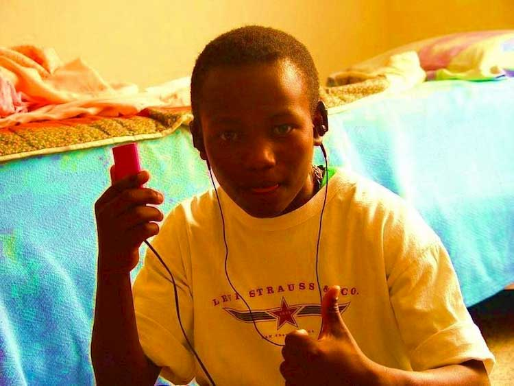 Wilson Kubwayo as a child with headphones and thumbs up