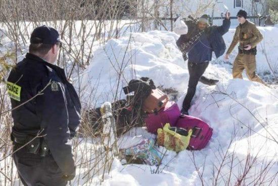 پناهجویان از مرز به سمت کانادا عبور میکنند، گارد مرزی آنها را نگاه می کند