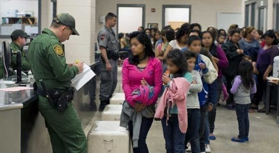 asylum seekers in immigration center with officials