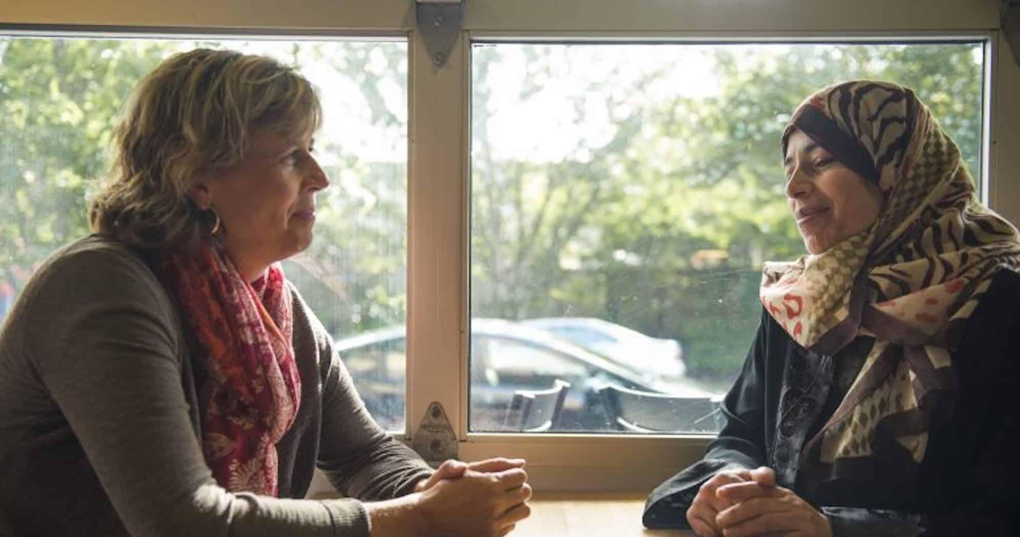一位金发女士和一位戴头巾的女士坐在窗边的桌子旁
