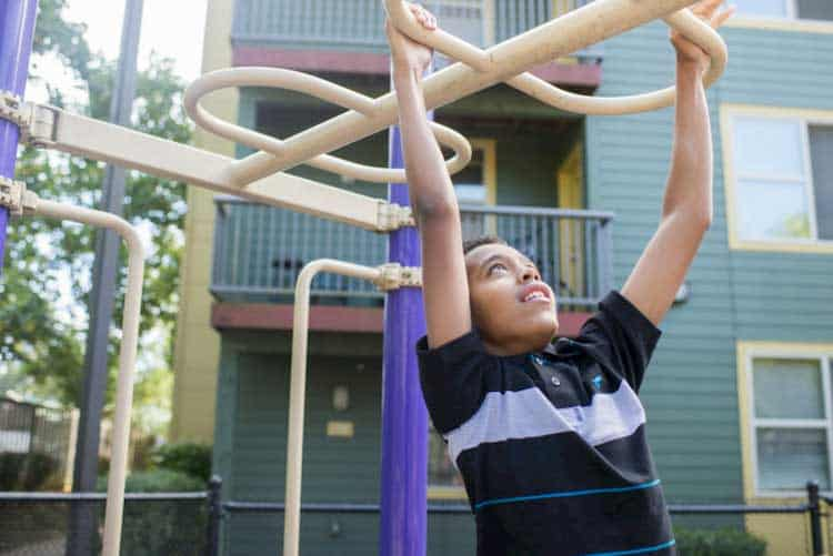 boy in striped shirt climbing at playground