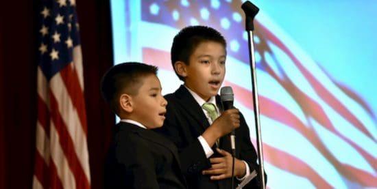 37/5000 niños cantando delante de banderas