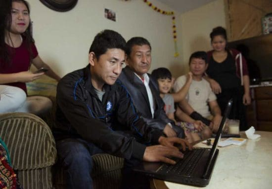 family group gathered around laptop at home
