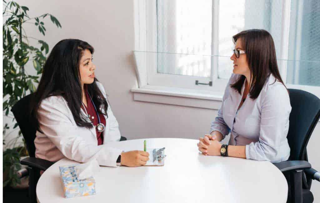 nữ bệnh nhân và bác sĩ ngồi ở bàn