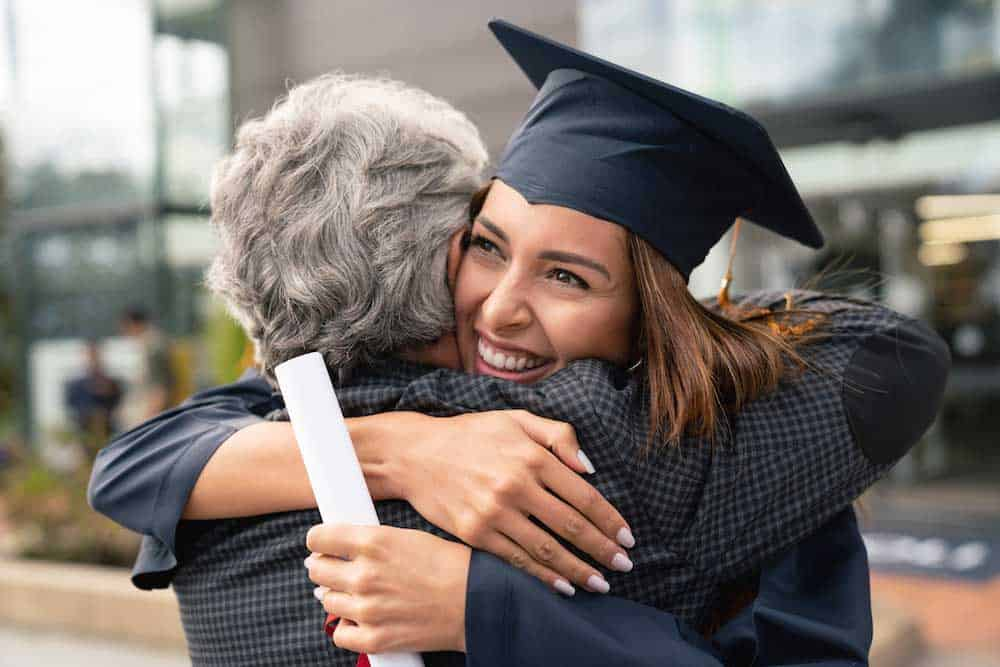 female graduate holding diploma and hugging senior