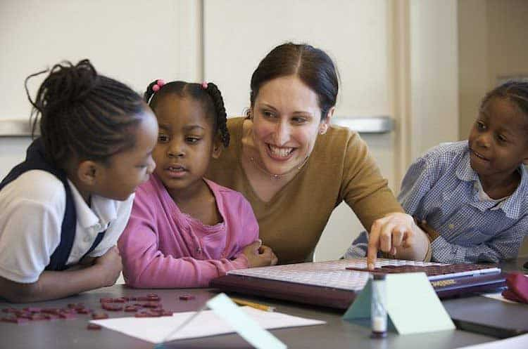 female teacher smiling at two young children in classroom