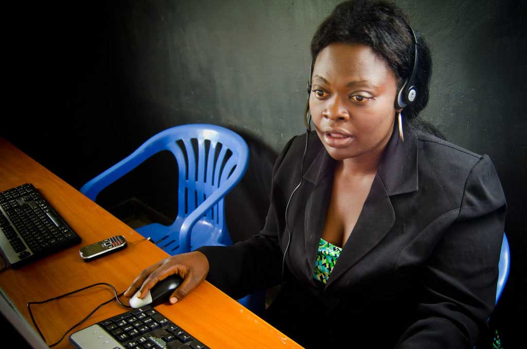 young woman wearing headphones with computer mouse in a blue chair