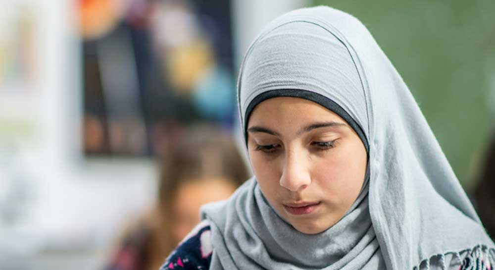 solemn girl in headscarf looking down