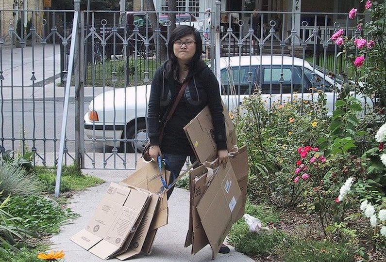 young woman standing outside with packing boxes
