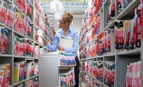 a female health inforamtion technician standing between to tall shelves and filing papers