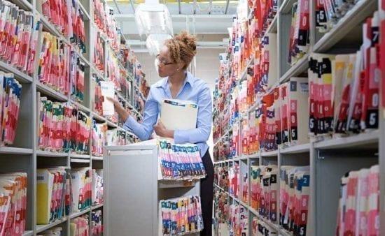 una técnica de información de salud femenina parada entre estantes altos y papeles de presentación