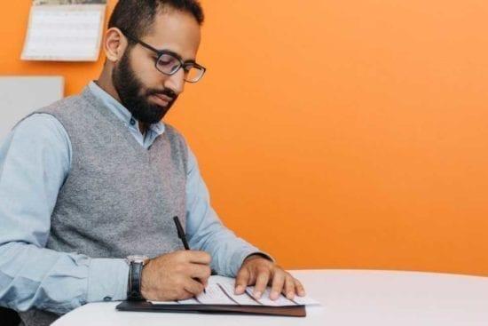 man filling out paper job application