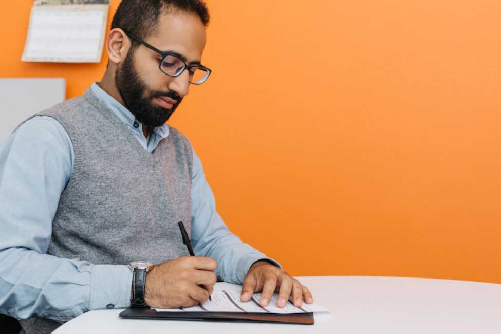 hombre llenando solicitud de trabajo en papel
