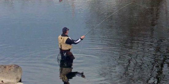 A man standing in water fly-fishing