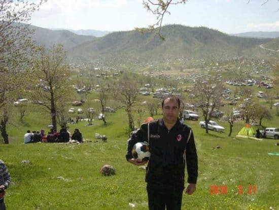 Man in hills holding soccer ball