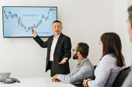 رجل يشير إلى الرسم البياني على الشاشة في المكتب