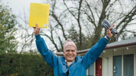 happy older man holding up yellow envelope