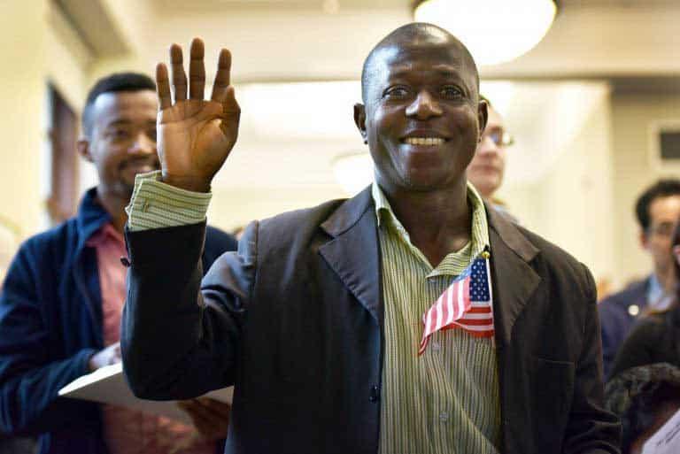 Un hombre con una bandera levantando la mano para tomar un juramento
