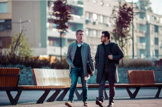two men walking and talking in a city park