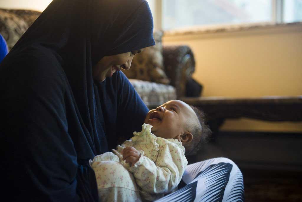 mẹ mỉm cười với bé ngồi trong lòng