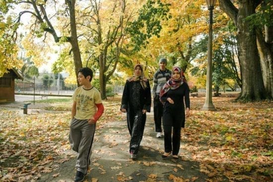 mother and three teenagers walking in the park in fall