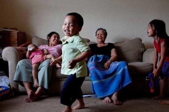 Madre y abuela riendo con tres niños pequeños