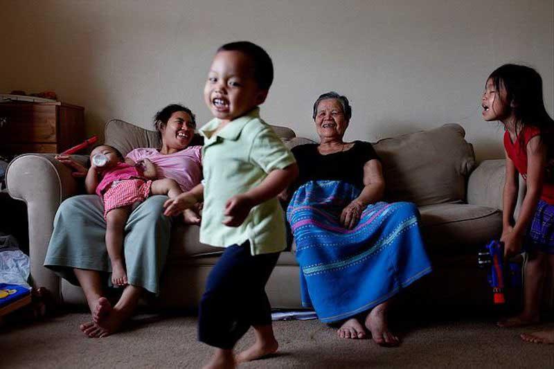 Mère et grand-mère riant avec trois petits enfants