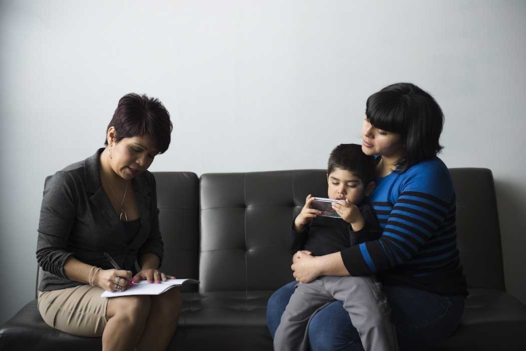 الأم والطفل الصغير على كنبة مع مستشار تدوين الملاحظات