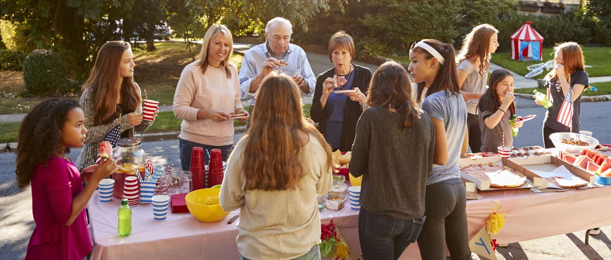 Neighbors share American food at an outdoor block party