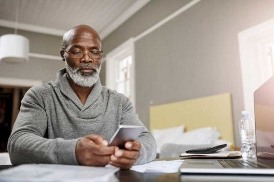 older man in grey sweater using a smartphone