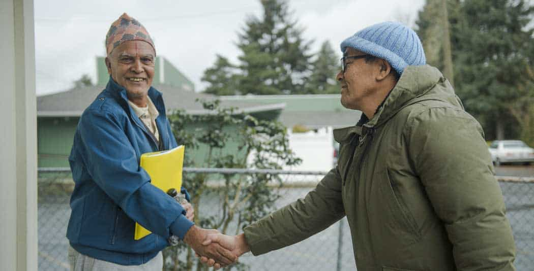two older men shaking hands and smiling