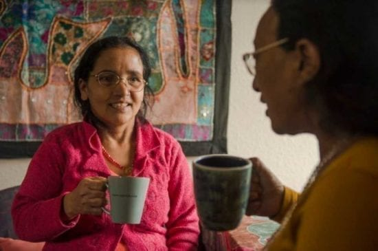 older women with cup at home talking to companion