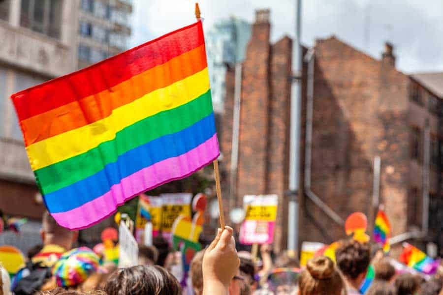 A large group of people march in a Pride Parade waving rainbow flags