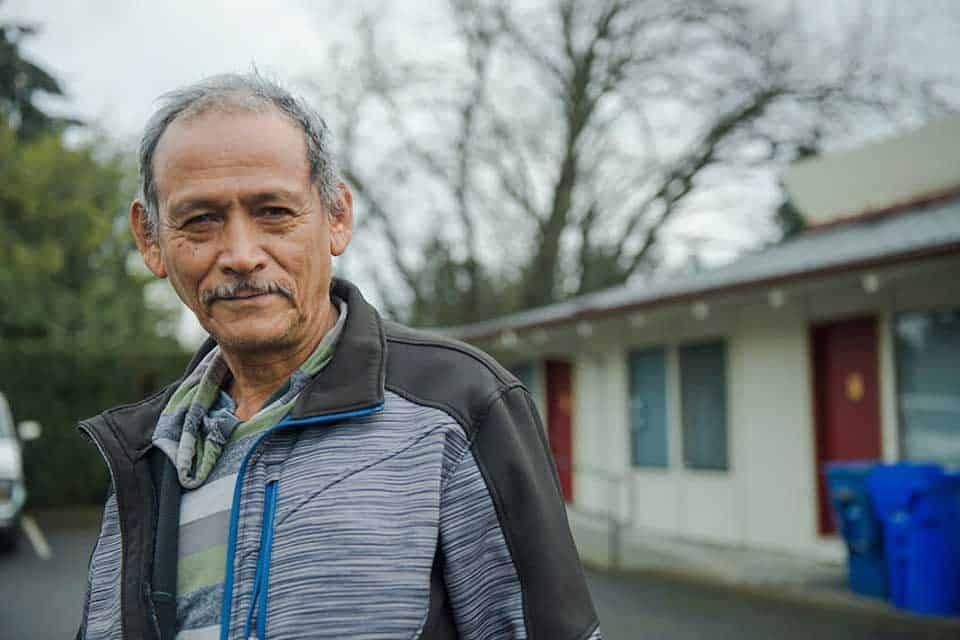 Homme plus âgé devant bâtiment bas