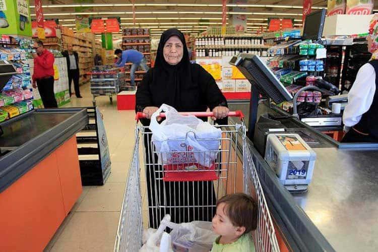 一位年长的女士推着购物车