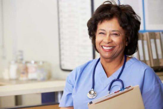 A smiling nurse holds patient files