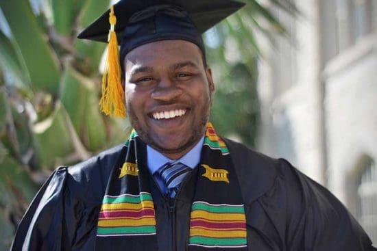 graduado masculino sonriente con borla amarilla