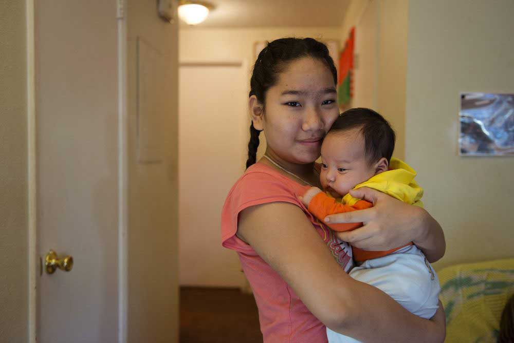 teenage girl holding baby
