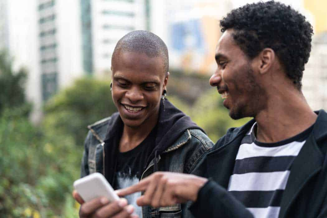 Une personne trans et son ami lisent des informations sur un smartphone