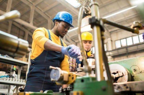 رجلان يعملان في الآلات الصناعية في ورشة عمل