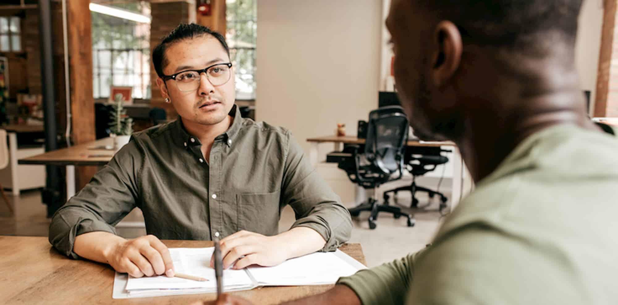 hai người đàn ông tư vấn tại bàn trong không gian làm việc lớn