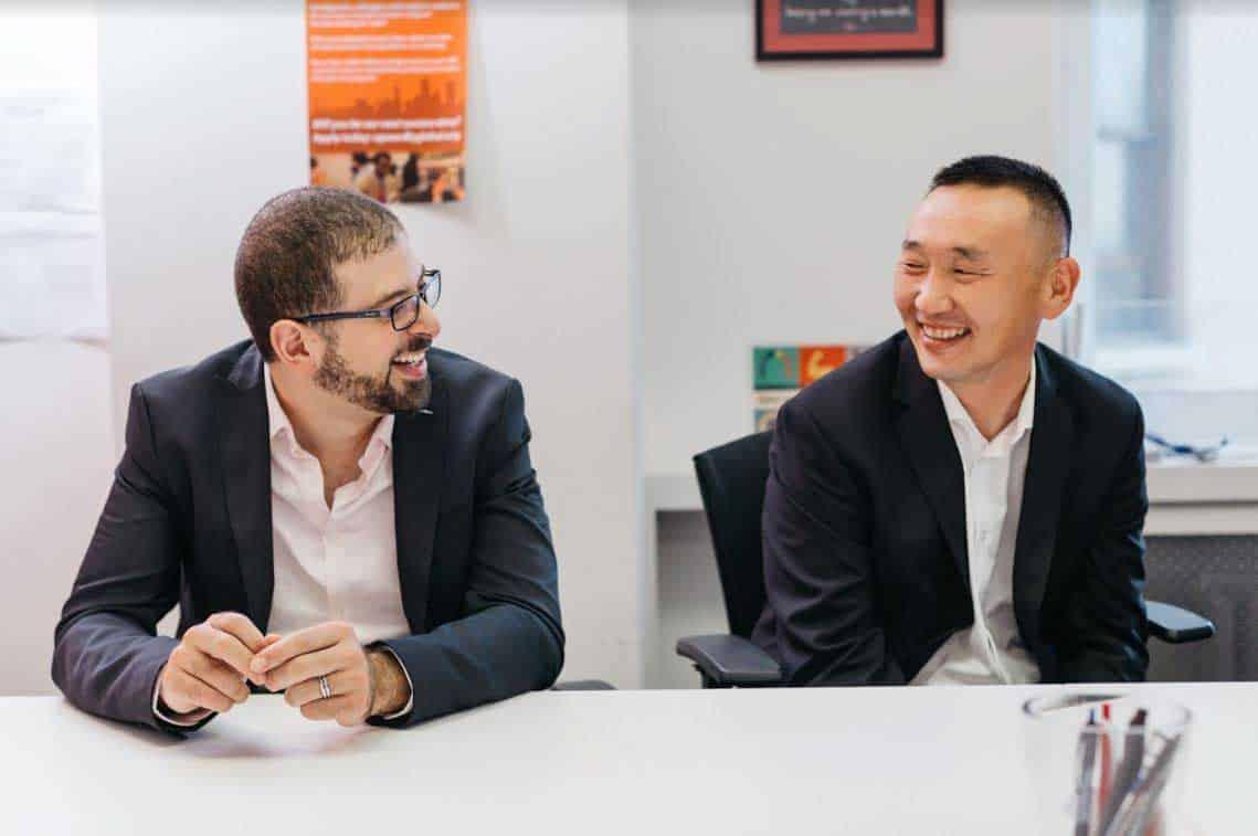 رجلان يبتسمان في بذلات يجلسان في غرفة المؤتمرات