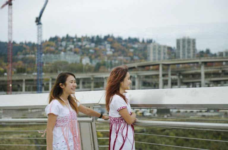 dos chicas de pie en un puente