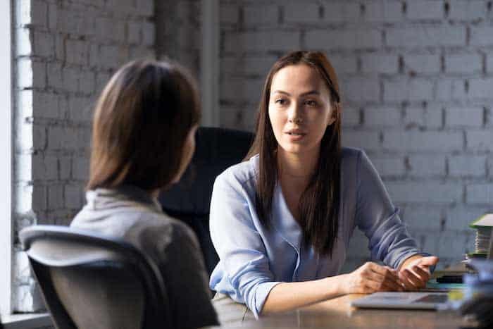dos mujeres consultan en la mesa frente a una pared de ladrillos
