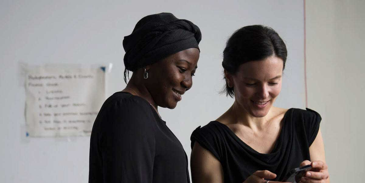 Two women are looking at a cellphone and smiling